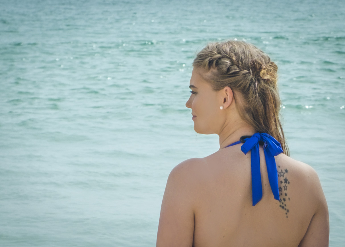 Girl wearing halto staring out to sea